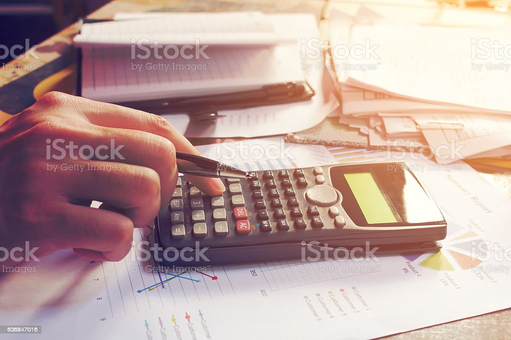 Close up man using calculator and doing finance in home​​​ foto