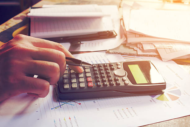 Close up man using calculator and doing finance in home - foto de acervo