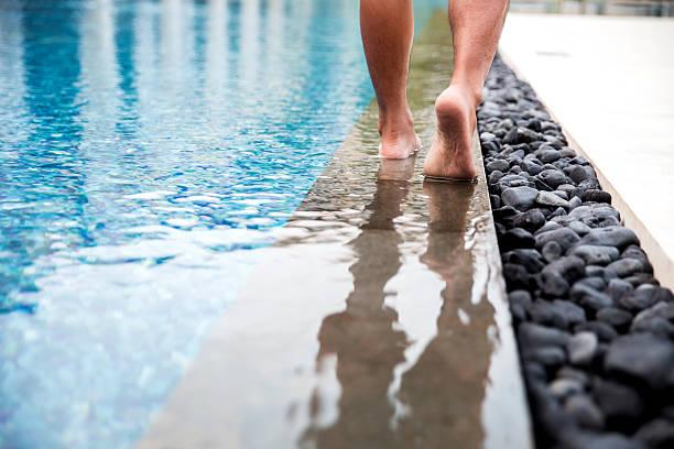 nahaufnahme des mannes gehen barfuß neben dem swimmingpool des hotels - pool schritte stock-fotos und bilder