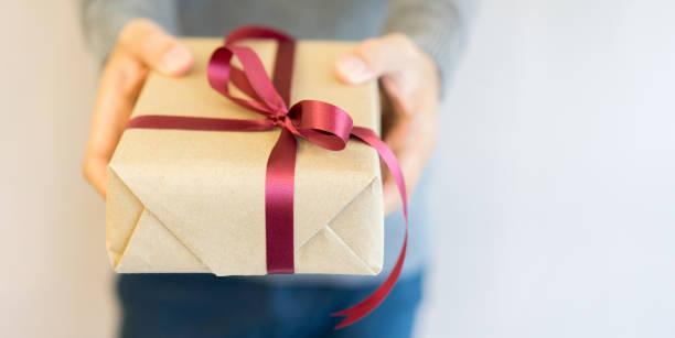 mann mit pullover und hand, die tan-box mit roter gebundene schleife geben geben, besondere person im wohnzimmer für frohe weihnachten und ein glückliches neues jahr festivalkonzept hautnah - heute ist freitag stock-fotos und bilder