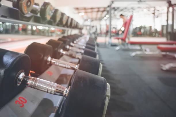 在運動健身中心的機架上關閉許多金屬啞鈴 - 健身房 個照片及圖片檔