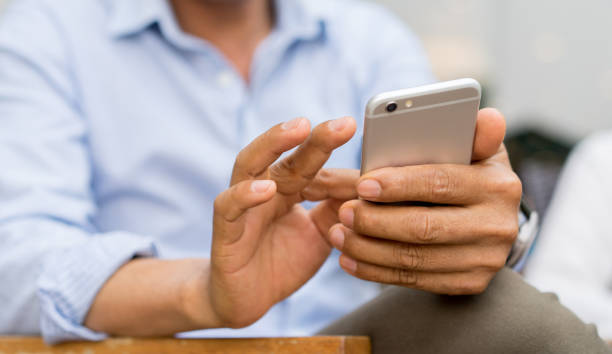close up mature businessman holding smartphone and checking news from company by texting to employee , business and technology concept - mandare un sms foto e immagini stock
