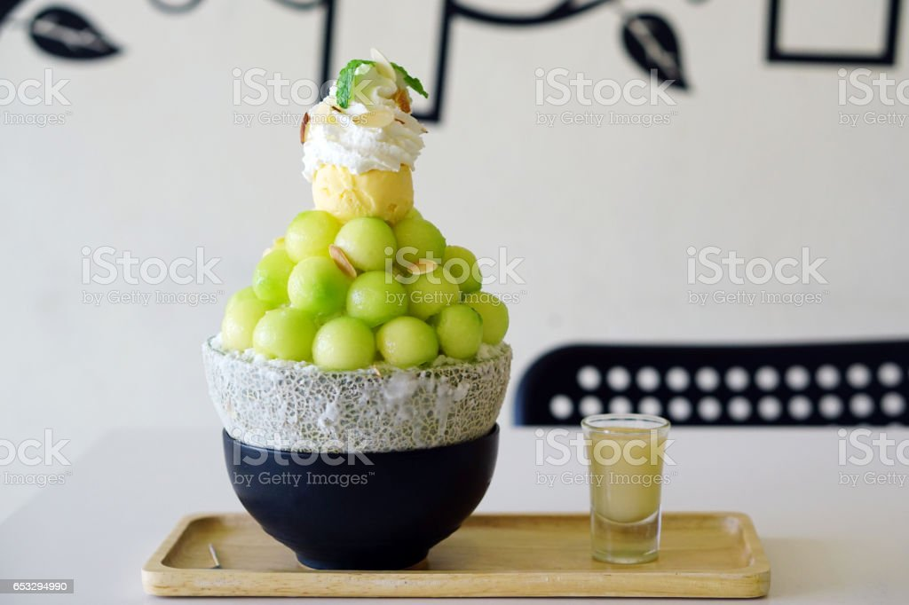 Close up Melon shaved ice or Melon Bingsu on wooden tray, Bingsu or Bingsoo is a Korean shaved ice dessert with sweet toppings such as ice cream vanilla, whipped cream and sweetened condensed milk. stock photo