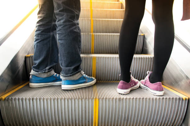 Close up Men wear jeans and woman on escalator stock photo