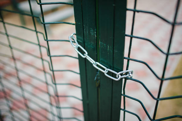 Close up metallic net-shaped green fence that closed and wrapped by chain stock photo