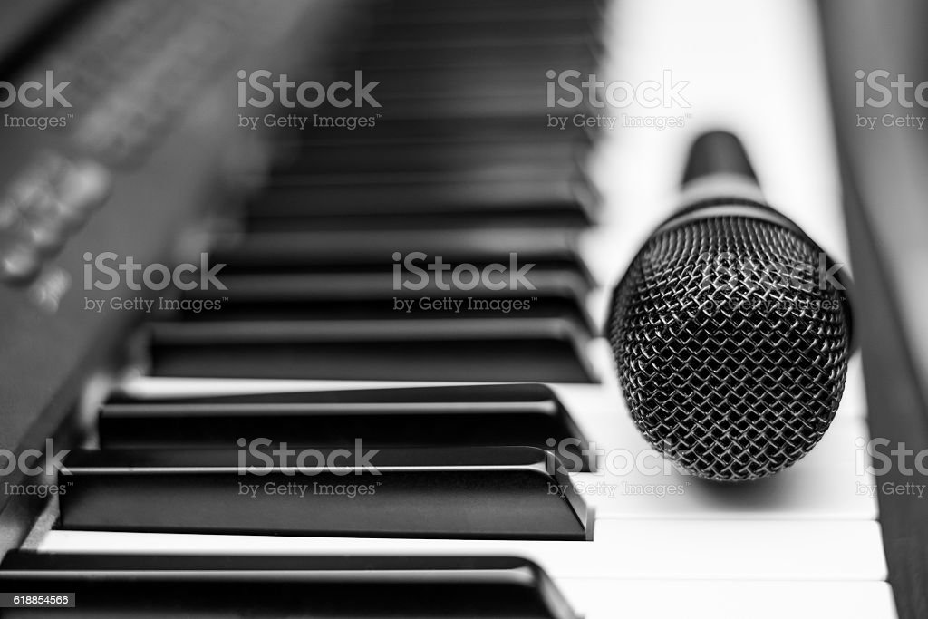 Close up microphone on piano keyboard in music studio. stock photo