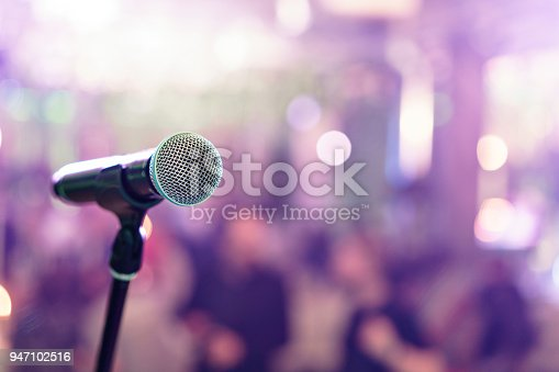 istock Close up microphone on stage in concert hall restaurant or conference room. Blurred background. Copy space 947102516
