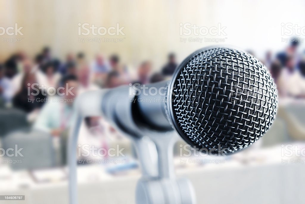 Close up microphone; seminar attendees in background - Royalty-free Anticipation Stock Photo