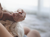 istock Close up Mother holding hands Asian female newborn baby  and sunlight in the morning. Cute little girl  three weeks old. Health, care, love, relationship concept. 1138322741