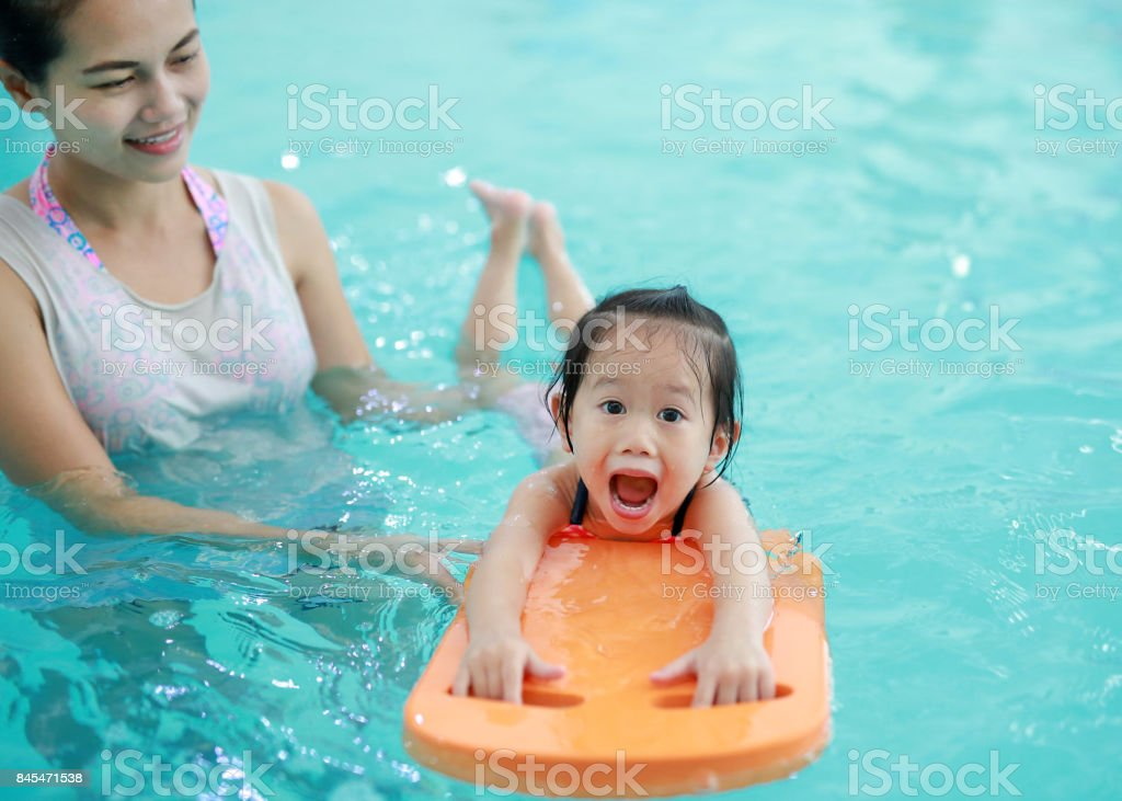 Close up mother teaching kid in swimming pool. stock photo