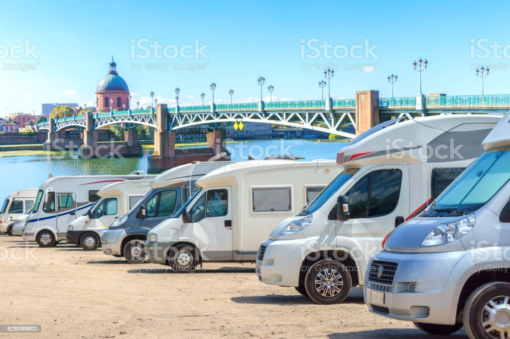 Close up motorhomes parked in a row on background The Saint-Pierre bridge passes over the Garonne river in Toulouse, France stock photo