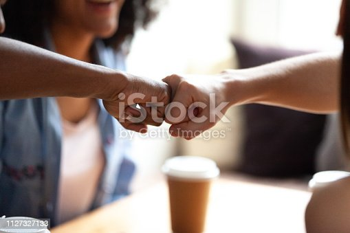 Close up multiracial best friends fist bumping, greeting each other, students celebrating successful exam results together, sitting in cafe, drinking coffee, symbol giving respect