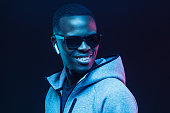 istock Close up neon picture of handsome African American man wearing wireless earphones and casual gray hoodie 1093991888
