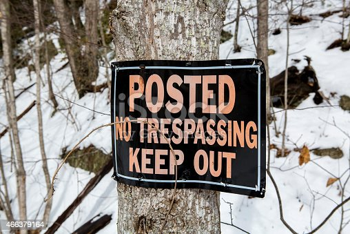 Close up photo of a No Trespassing sign. The letters were orange on a black bacground, but have faded from years of being in the sun. The warning sign is nailed to a tree and most of the sign is hanging off the edge. In the background are more trees with snow on the ground. A cool looking weathered sign.