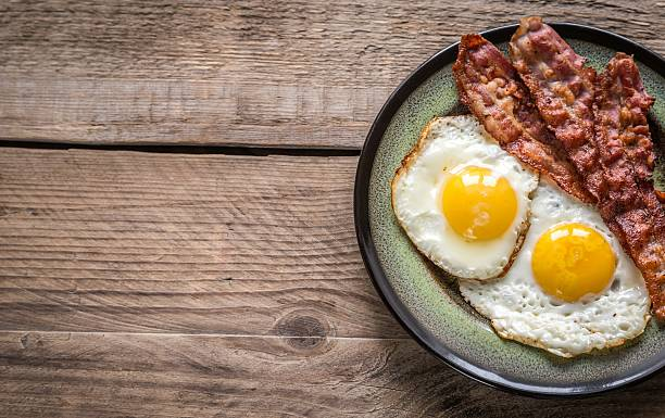 Close up of 2 sunny side up style eggs and bacon on a plate stock photo
