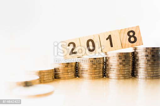 istock Close up of 2018 number wooden block with stack of coins on white background. 814642422