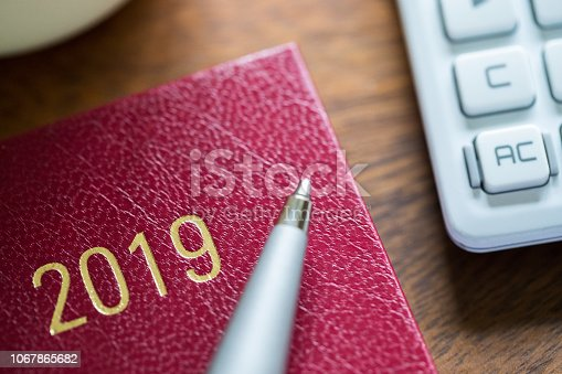 istock Close Up Of 2019 Diary With Pen And Calculator On Wooden Desk 1067865682