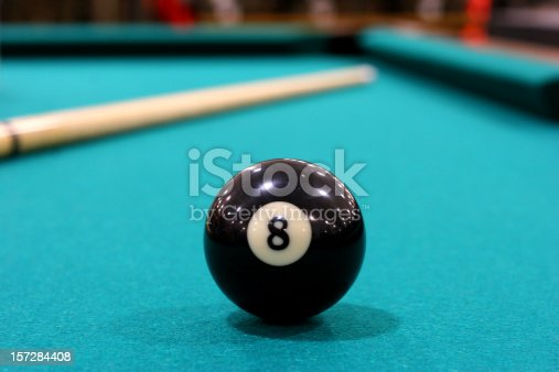 Eight ball on pool table with cue visible