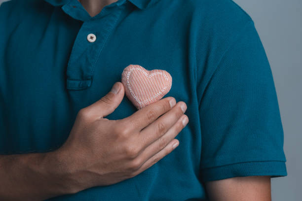 close up of a a man holding a red heart cloth in his hands. stock photo