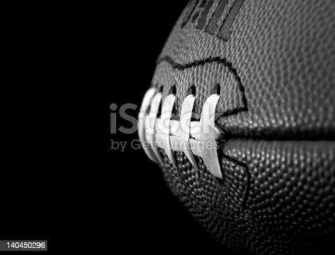 Black & white close up of an american football on a black background.