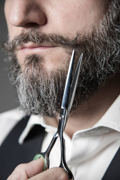 close up of a barber adjusting his mustache with a pair of scissors close-up image depicting the act of correcting whiskers with barber scissors facial hair stock pictures, royalty-free photos & images