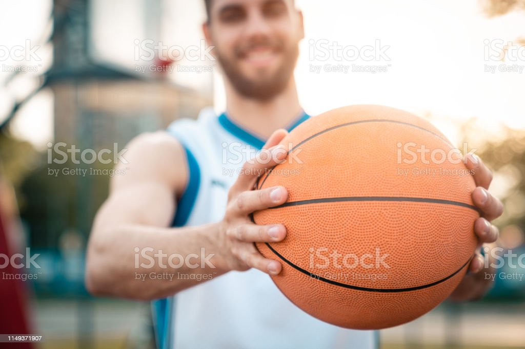 Close up of a basketball player holding a basketball. Sports ball....