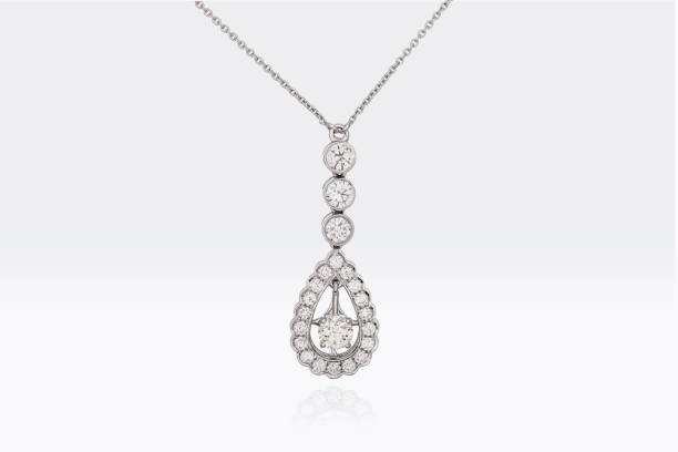 close up of a beautiful round and pear shape diamonds pendant in white platinum gold isolated on white background - ожерелье стоковые фото и изображения