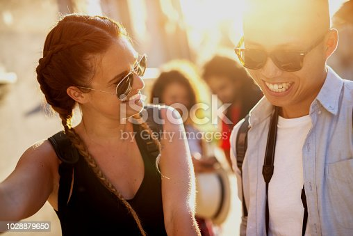 507375092istockphoto Close up of a beautiful young couple laughing on a street and having fun with their friends standing behind them. 1028879650