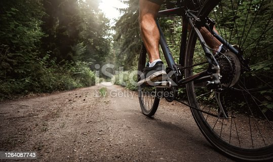 Close up of a biker riding a bike through the forest road