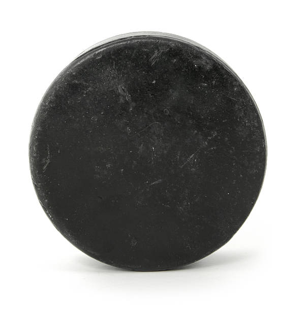 close up of a black hockey puck - hockey puck stock photos and pictures
