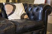 Close- up of a black leather sofa and cushion