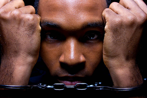 Close Up of a Black Man in Hand Cuffs stock photo