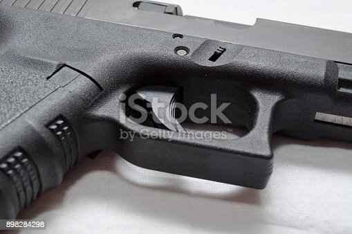 A close up of a black semi automatic pistol, showing the trigger, trigger guard, grip and ejection port