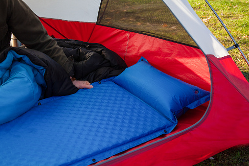 A man gets his tent and sleeping bag ready at a campground by inflating and setting up his blue blow-up mattress pad to put for under his sleeping bag