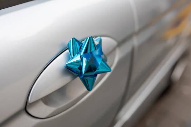 nahaufnahme von einem blauen hochzeit bogen am griff eine silberne hochzeit auto - autoschleifen stock-fotos und bilder