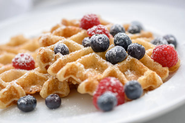 Close up of a blueberry and raspberry topped waffles Close up of a black waffle iron with waffle sprinkled with powedered surger. waffle stock pictures, royalty-free photos & images