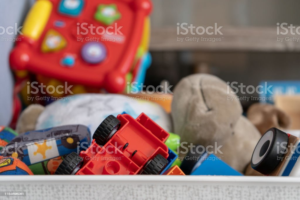 Close up of a box of toys, with many different objects including soft...