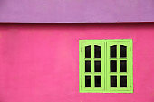Close up of a brightly coloured building with pink walls, lime green windows & purple roof, Caribbean.