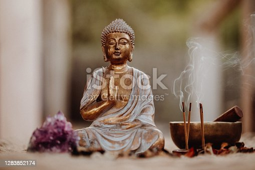 istock Close up of a Buddha figurine and smoky incense with gong and amethyst 1283852174