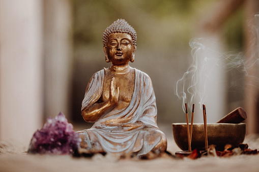 Close up of a Buddha figurine and smoky incense with gong and amethyst. Focus on the Buddha and the incense.