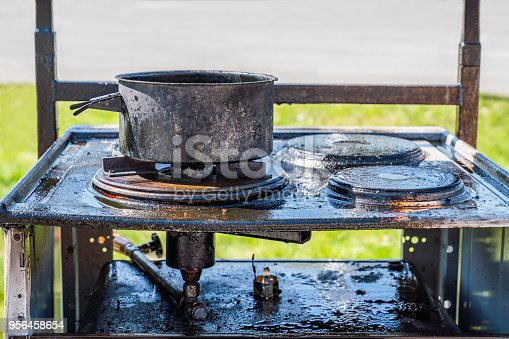 istock Close up of a burnt black gas stove covered with grease, a burnt pot on top. 956458654