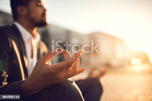 Close up of African American businessman meditating in Lotus position at sunset.