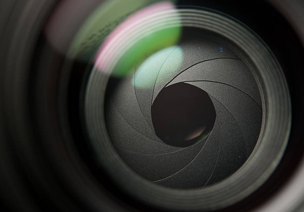 A close up of a camera lens partially open stock photo