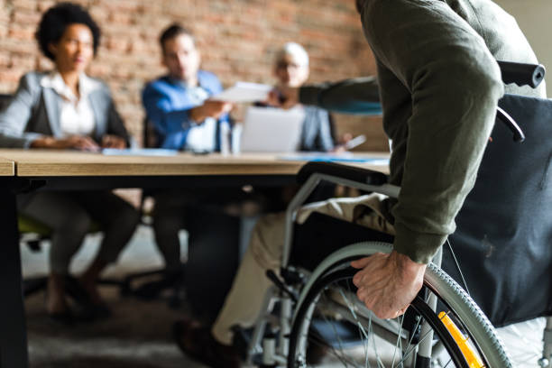 Close up of a candidate in a wheelchair on a job interview. Close up of unrecognizable candidate in a wheelchair on a job interview in the office. persons with disabilities stock pictures, royalty-free photos & images