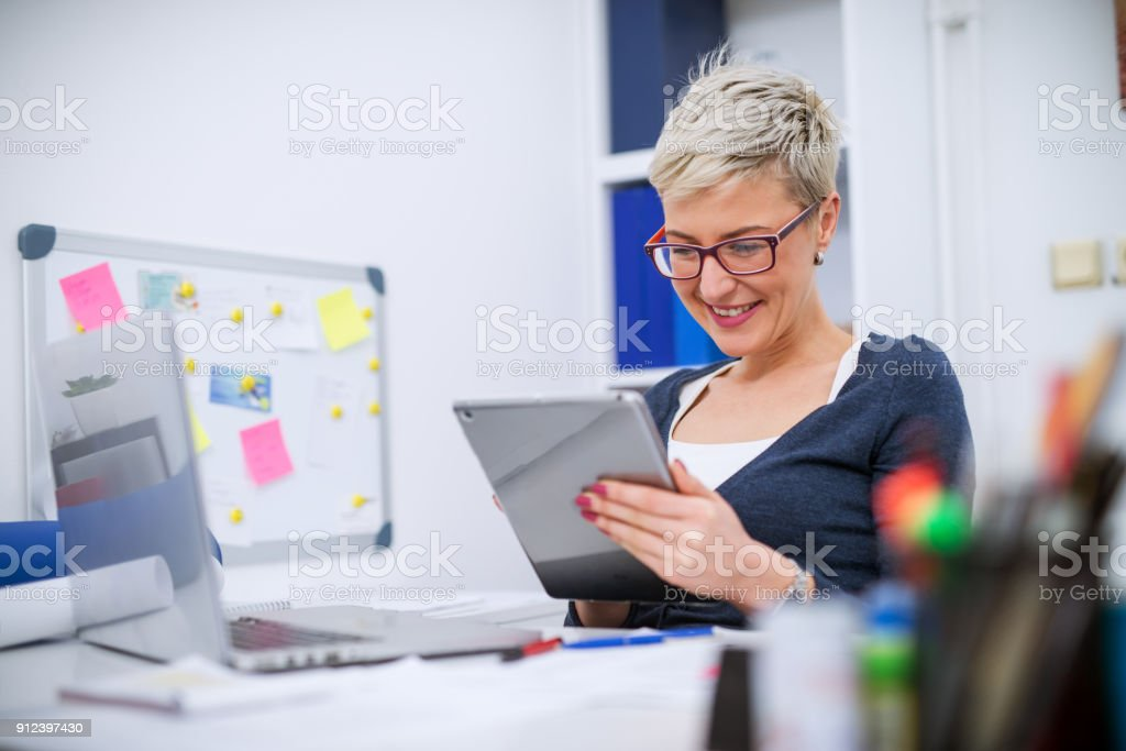 Close up of a charming satisfied professional short hair manager woman sitting in the office and looking in a tablet. stock photo