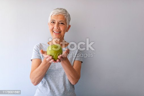 1173001813istockphoto Close up of a cheerful elderly woman eating an apple while smiling 1173001592