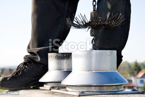 Close up of a chimney sweep on top of the chimney. Wearing the traditional workwear and holding a rope with the broom inside of the chimney. Clear sky in the background.
