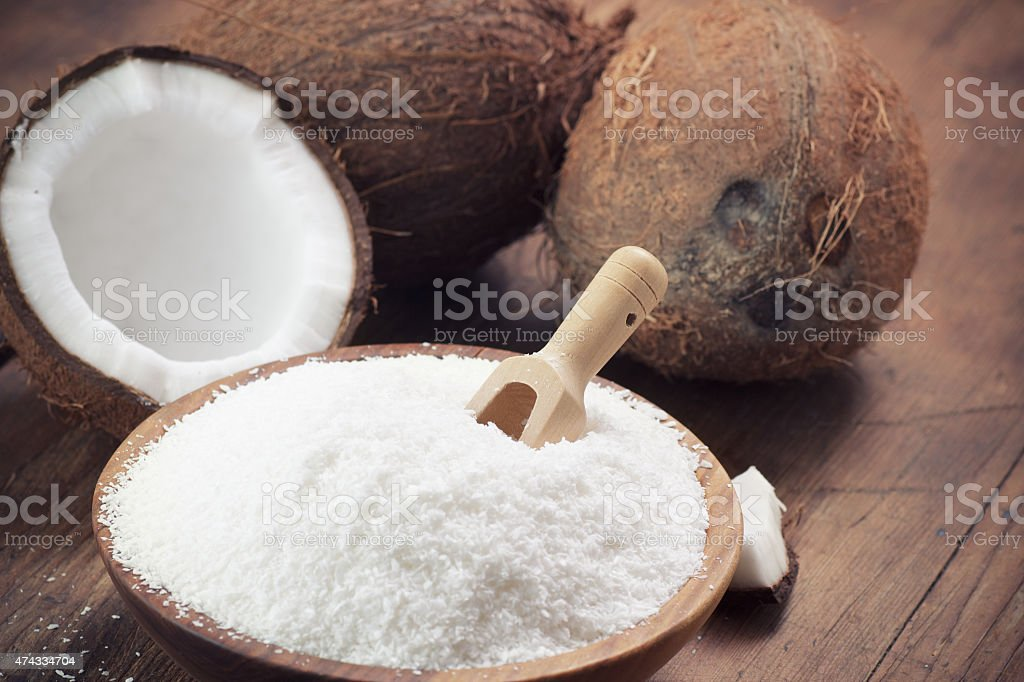 Close up of a coconut and grounded coconut flakes stock photo