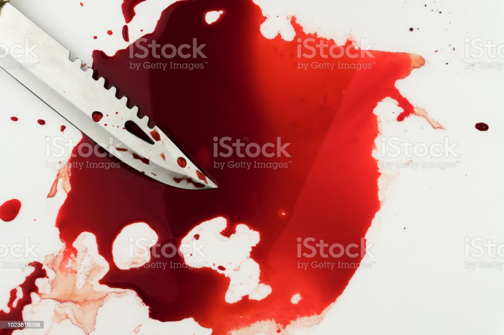 close up of a combat knife in pool of blood stock photo