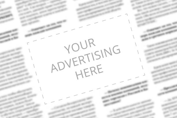Close up of a copy space with wrtitten words Your Advertising Here on a blurred background of a newspaper. Business concept. Adding ad into paper page. Mockup of a newspaper advertisement column stock photo